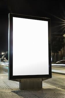 Panneau d'affichage vide avec écran blanc sur le trottoir de nuit