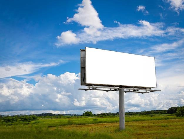 Panneau d'affichage vide en face de beau ciel nuageux dans une zone rurale