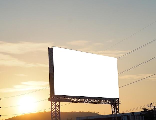Panneau d'affichage vide sur fond de coucher de soleil pour la nouvelle publicité