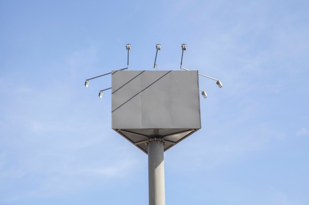 Panneau d'affichage vide avec des lumières contre le ciel bleu