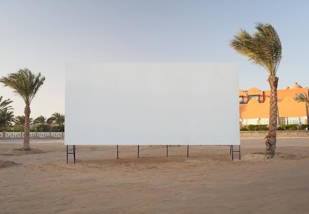 Panneau d'affichage vide avec des palmiers