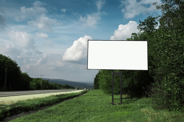 Panneau d'affichage vide pour l'affiche publicitaire près de la route asphaltée et de la forêt verte, sur fond de ciel bleu.
