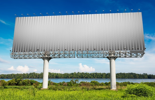 Panneau d'affichage vide pour la publicité au bord de la rivière et le ciel bleu