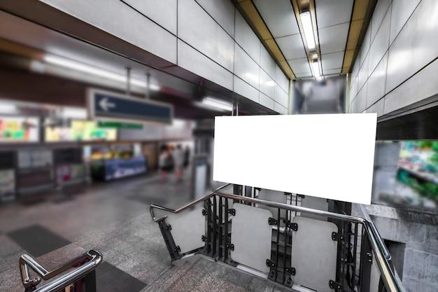 Panneau d'affichage vide prêt pour une nouvelle publicité sur les escaliers à l'extérieur à la station de métro aérien