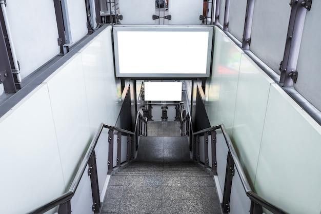 Panneau d'affichage vide prêt pour une nouvelle publicité pour les services d'information à la clientèle dans les escaliers extérieurs à la station de skytrain