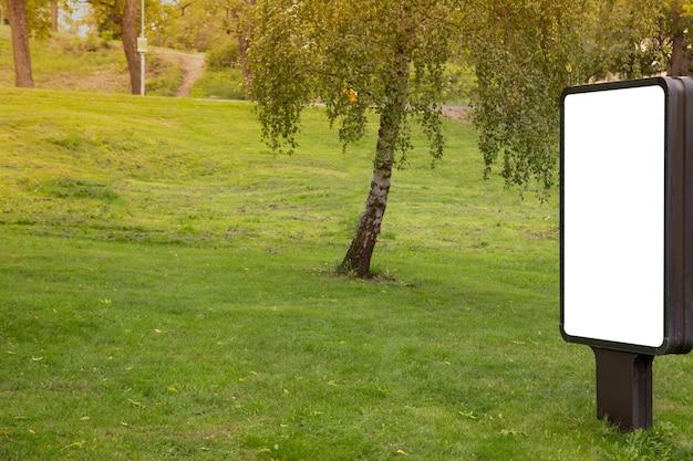 Panneau d'affichage vide simulé sur un parc public pour un message texte ou un contenu.