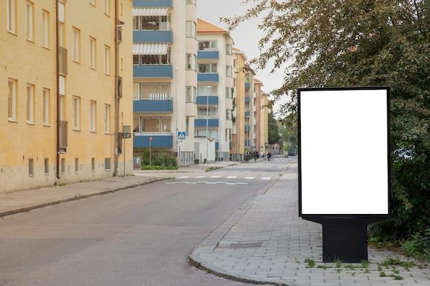Panneau d'affichage vide simulé sur la route de la ville pour un message texte ou du contenu.