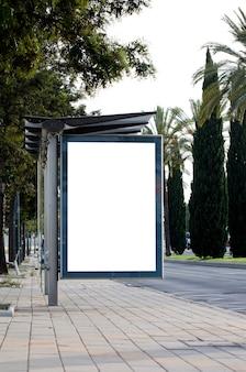 Panneau d'affichage vide vertical dans la rue de la ville avec des arbres verts