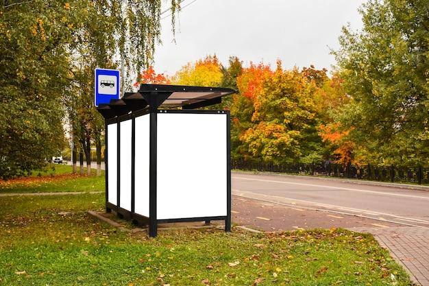Panneau d'affichage vierge à l'arrêt de bus de la ville un jour d'automne panneau d'affichage vierge vertical à côté de la route du trottoir