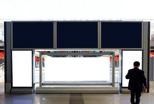 Panneau d'affichage vierge et bannière avec homme d'affaires à l'aéroport
