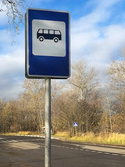 Panneau d'arrêt de bus bleu sur le côté de la route