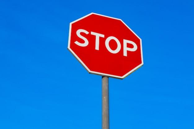 Panneau d'arrêt rouge en ville close up