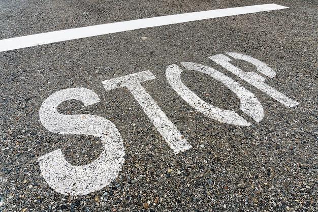 Panneau d'arrêt sur la route avec de l'asphalte texturé