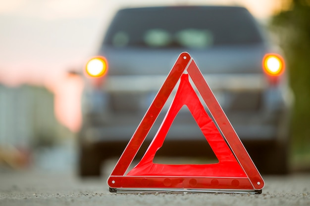 Panneau d'arrêt triangle rouge d'urgence et voiture cassée dans une rue de la ville.