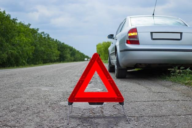 Panneau d'arrêt d'urgence rouge et voiture d'argent cassée sur la route