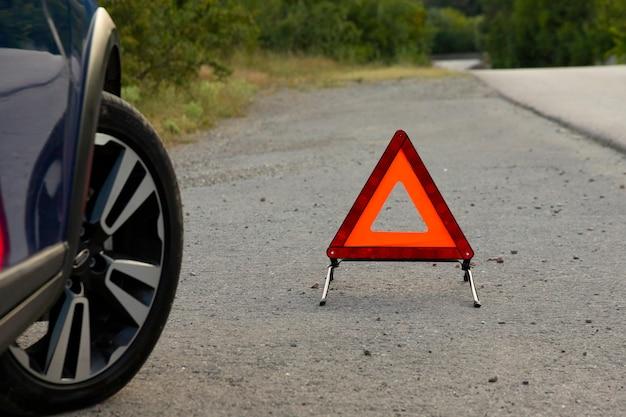 Un panneau d'arrêt d'urgence d'un véhicule est installé sur la route, à côté de la voiture. espace de copie.
