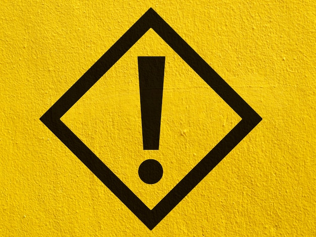 Un panneau d'avertissement d'avertissement noir peint sur un mur de stuc à l'extérieur