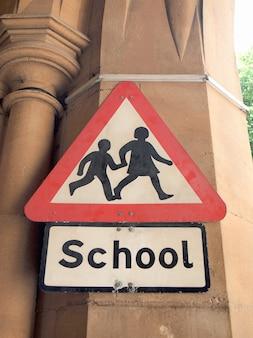 Panneau d'avertissement de l'école sur un mur du bâtiment