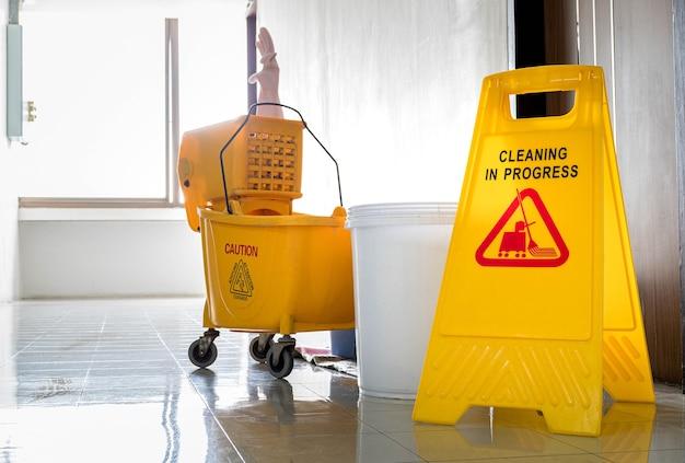 Panneau d'avertissement jaune avec message nettoyage en cours avec chariot de nettoyage