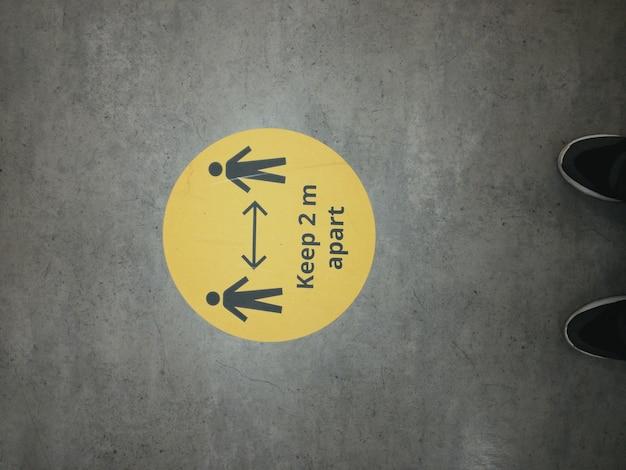 Panneau d'avertissement jaune pour maintenir la distance pendant l'épidémie de coronavirus covid-19 avec des chiffres d'hommes en magasin et des jambes d'une personne au royaume-uni