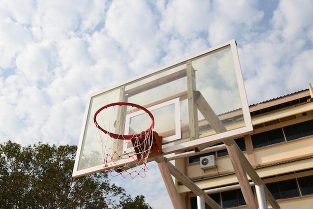 Panneau de basket avec cerceau de basket et beau ciel en journée ensoleillée.