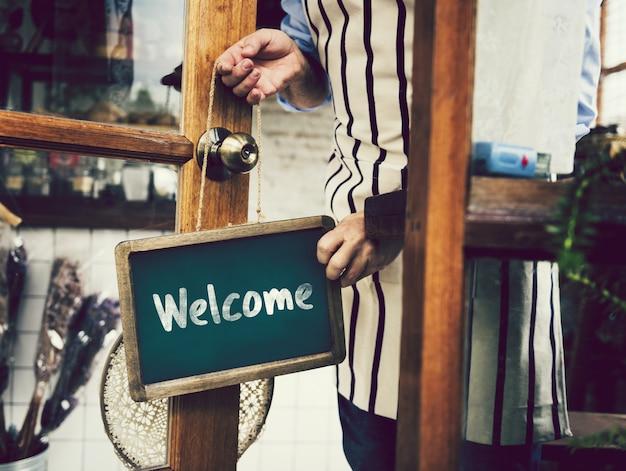 Panneau de bienvenue accroché à une porte vitrée