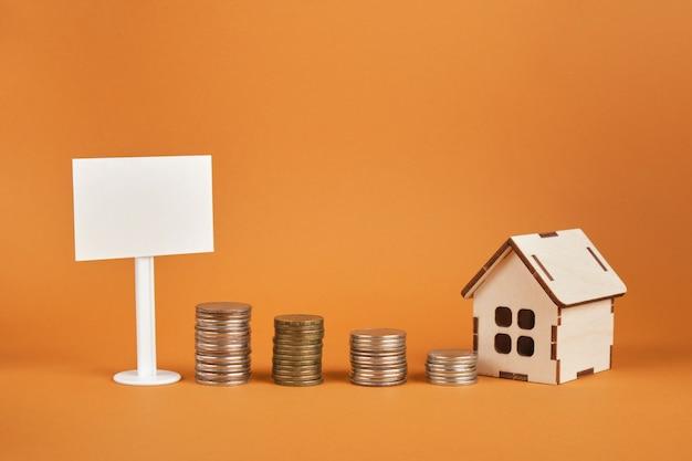 Panneau blanc blanc, modèle de maison et tours de pièces de monnaie sur fond marron
