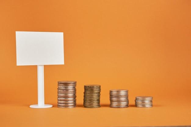 Panneau blanc blanc et tours de pièces de monnaie sur fond marron
