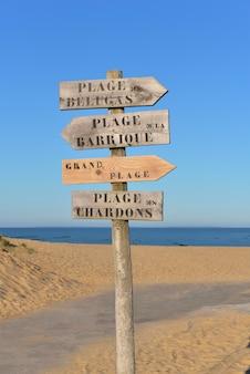 Panneau en bois dans le sable indiquant en français