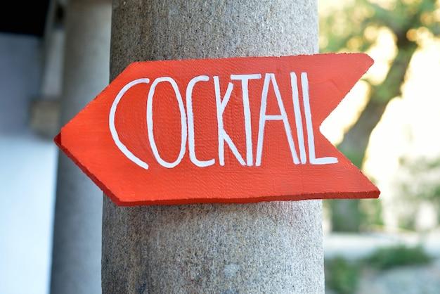 Panneau en bois avec flèche rouge indiquant l'adresse du cocktail