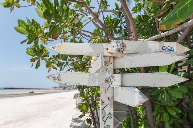 Panneau en bois de flèches sur la plage avec plante verte