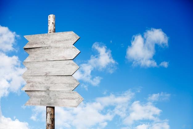 Panneau en bois sur fond de ciel bleu avec des nuages
