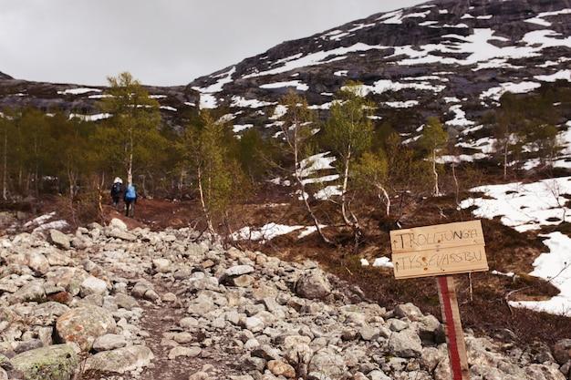 Panneau en bois avec le lettrage «trolltunga» se dresse sur le chemin vers les montagnes