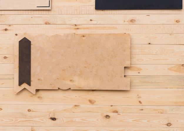 Panneau en bois rustique vierge avec flèche et espace de copie pointant vers le haut accroché à un mur en bois dans une vue d'arrière-plan plein cadre