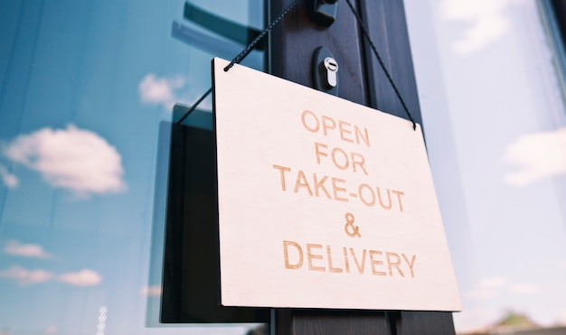 Panneau en bois avec texte: ouvert pour emporter et livraison accroché à la porte au café