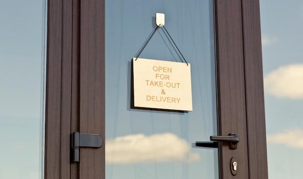 Le panneau en bois avec texte: ouvert pour emporter et livraison accroché à la porte du café