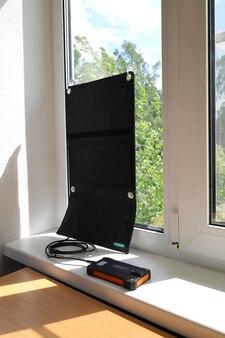 Le panneau de chargeur solaire sur la fenêtre charge le powerbank