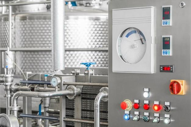 Panneau de commande avec boutons et réservoir dans une usine de boissons