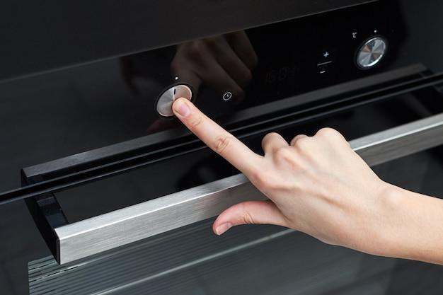Panneau de commande tactile main femme sur four électrique dans la cuisine
