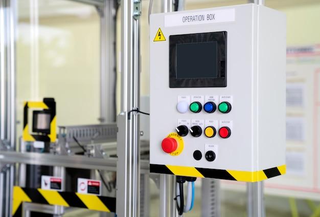 Panneau de contrôle de la machine à tester avec bouton d'urgence.