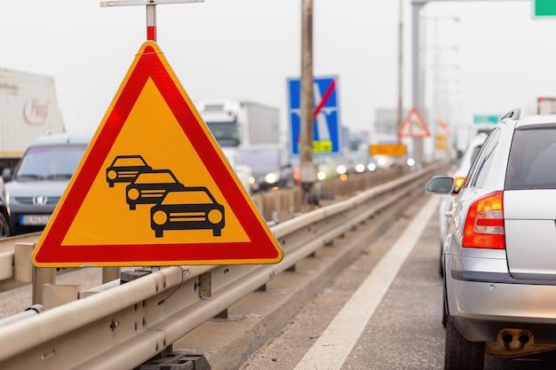 Panneau d'embouteillage sur une autoroute avec une file de voitures en attente dans la rangée