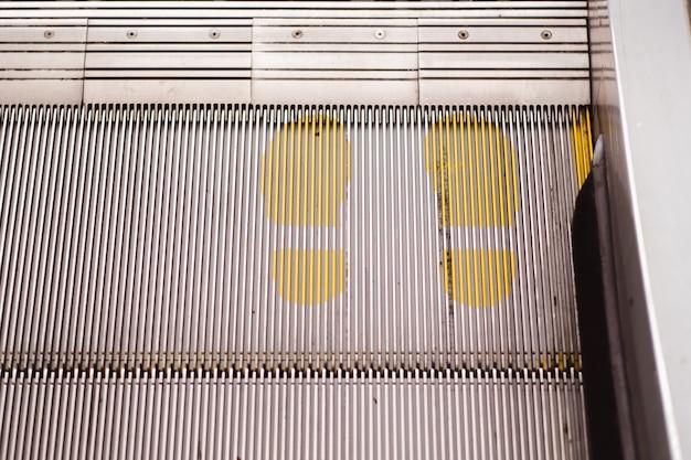 Panneau d'impression de point de pied sur l'escalator en jaune pour maintenir la distance pendant la pandémie de covid-19