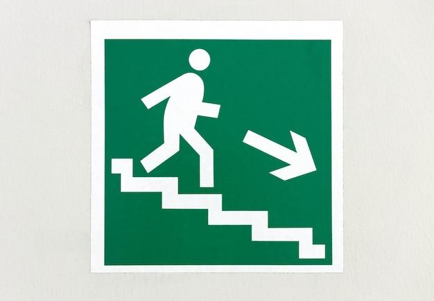 Un panneau indiquant où aller avec un homme descendant les escaliers