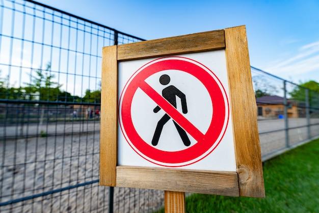 Panneau d'interdiction pour les piétons à côté de la clôture