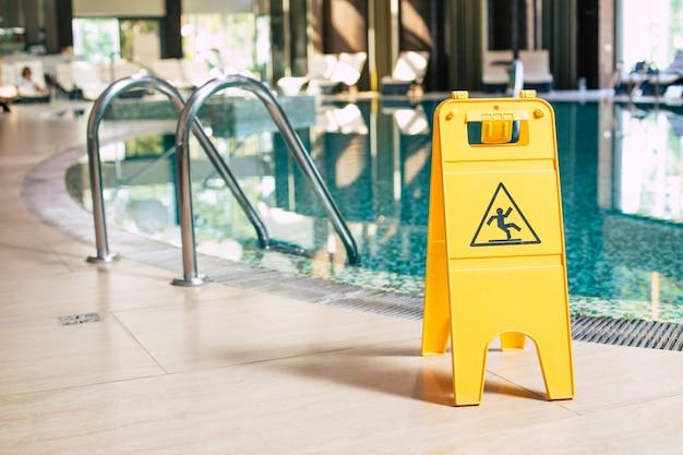 Panneau jaune de plaque de sol humide près de la piscine.