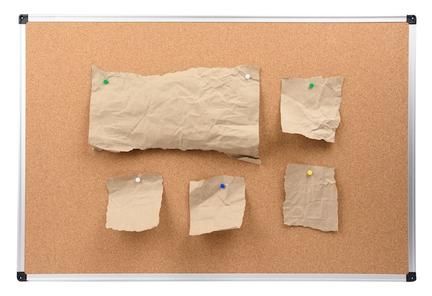 Panneau de liège avec cadre en aluminium et morceaux de papier brun attachés, conseil isolé sur fond blanc