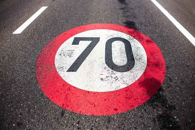 Panneau de limitation de vitesse à 70 km / h peint sur route asphaltée.