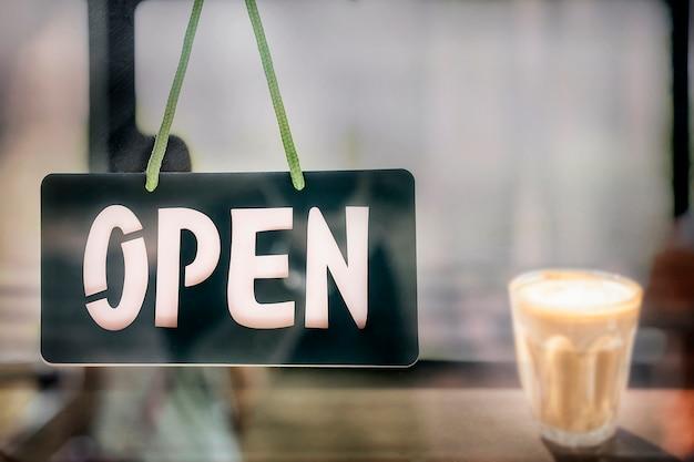 Panneau ouvert accroché à la porte du café.