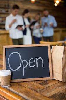 Panneau ouvert avec tasse à café jetable et sac en papier sur la table à la cafétéria