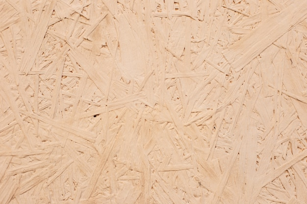 Panneau de particules beige close-up texture fond bois. proche